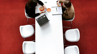 Photo from top showing 2 Henkel employee sitting at a white table