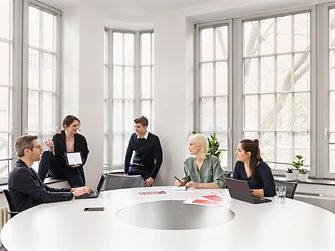 5 people talking to each other sitting and standing around a white table in a Henkel meeting room with high windows