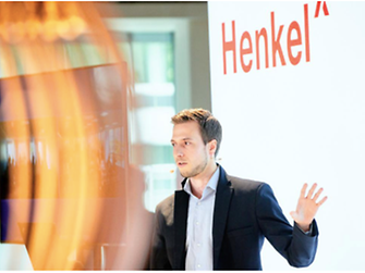 Employees standing in front of a screen with the word Henkel displayed, holding a presentation